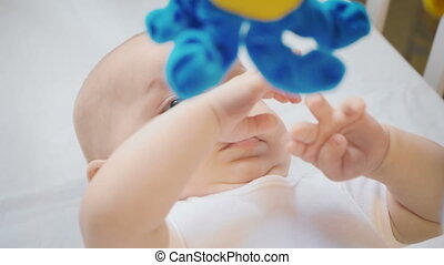 Video of lying baby four month girl playing with mobile -...