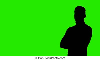 Video of man's silhouette with arms crossed and copyspace on green background