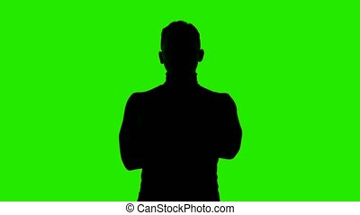 Video of man's silhouette with arms crossed on isolated green background