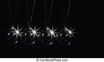 Video of newton's balls with light's reflection on black background