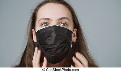 Video of panic woman dressing medical masks on grey background