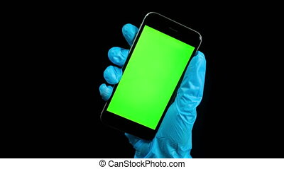 Footage of person wearing latex protective glove holding cell phone with green screen on monitor against a plain black background