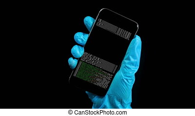 Footage of person wearing latex protective glove holding cell phone with data code on monitor against a plain black background
