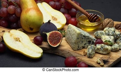 Video of roquefort or dorblu cheese and grapes on wooden...