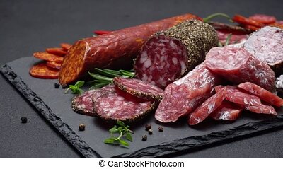 salami and chorizo sausage close up on stone serving board -...