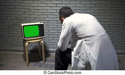 Video of man watching retro tv on wall background
