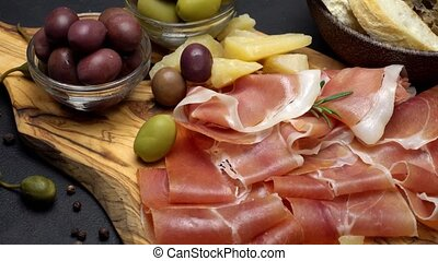 sliced prosciutto on a wooden board and bread