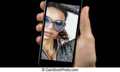 Footage of person holding mobile phone with video of sexy woman posing with sunglasses