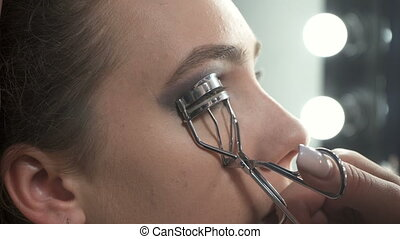 Video of visagist using eyelash curler in beauty studio