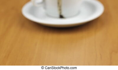 Video of white cup with coffee is on the table. Dolly shot. Close-up.