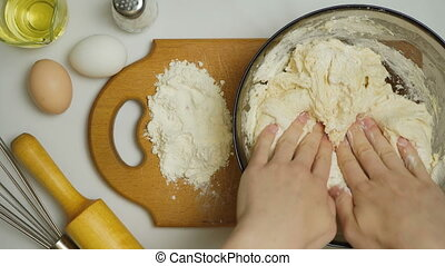 Video of woman kneads dough in the kitchen