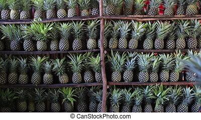 Video of a woman putting a pineapple on a shelf that is full of pineapples in Mexico