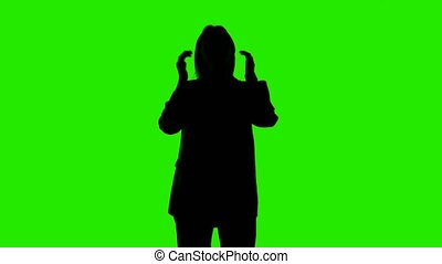 Video of woman's rolling sleeves silhouette in suit jacket on green background
