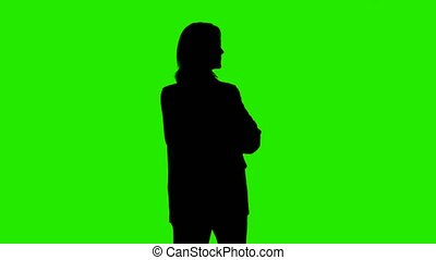 Video of woman's silhouette in suit jacket with arms crossed on green background
