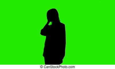 Video of woman's silhouette in suit jacket with facepalm gesture on green