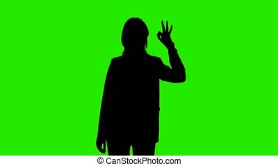 Video of woman's silhouette in suit jacket with ok gesture on green background