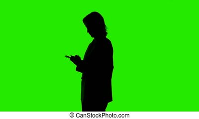 Video of woman's silhouette in suit jacket with smartphone on green background