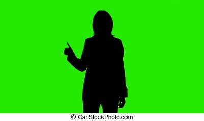 Video of woman's silhouette in suit jacket with thumb gesture on green