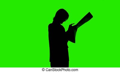 Video of woman's silhouette with newspaper on isolated green background