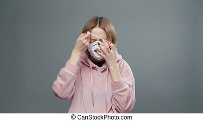 Video of young sneezing woman with medical mask