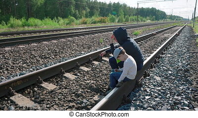 Video of young woman and boy sitting on rails - Video of ...