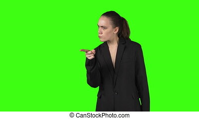 Video of young woman in black jacket on green isolated background