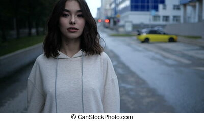 Video portrait of a cute girl looking at the camera, straightening her hands with dark hair up to her shoulders in a beige hoodie against the backdrop of the cityscape and yellow car