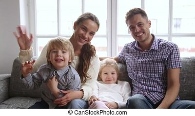 Video portrait of happy family with two kids waving hands