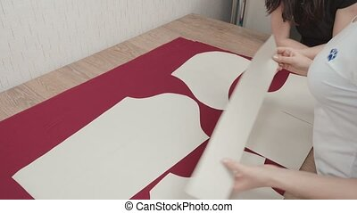 Video of seamstress drawing curve line on fabric in workshop