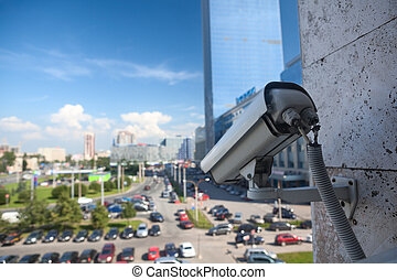 Video surveillance camera on a wall looking at street parking zone