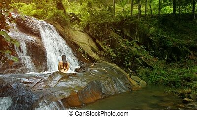 A woman bathes in the forest waterfall