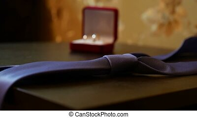 video wedding rings and a blue tie on the table