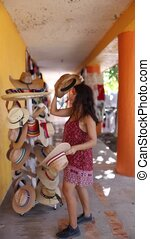 Portrait Orientation Video of a woman trying traditional Mexican hats, made of straw and colorful fabrics at a shop in Mexico