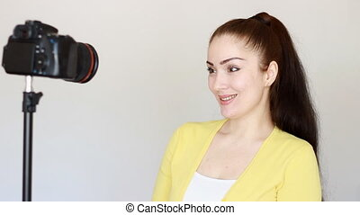 Videoblog, vlog, vlogger, blog, blogging, Video, mass media and interview. Smiling young woman or bloger gestures with hands and speaks,recording video on a camera that is fixed to a tripod in the studio.