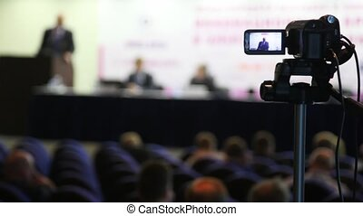 videocamera keeps record of performance of lecturer in presentation hall