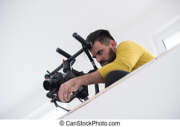 videographer at work - young videographer with gimball video...