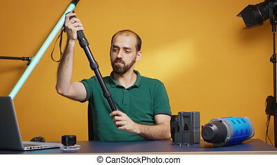 Videographer recording tutorial of monopod for professional content creators. Professional studio video and photo equipment technology for work, photo studio social media star and influencer