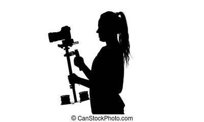 Videographer shoots video in the studio. White. Silhouette