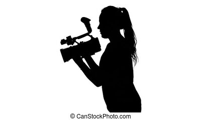 Videographer works with a professional camera. White. Silhouette