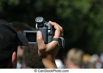 A man videotapes an event.
