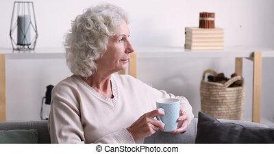 vieille femme, thé, maison, décontracté, regarder, boire, heureux, loin