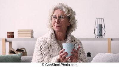 vieille femme, thé, sourire, appareil photo, maison, regarder, boire