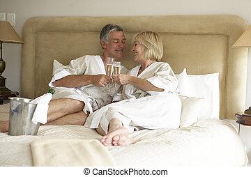 vieilli, couple, milieu, chambre à coucher, champagne, apprécier