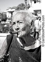 viejo, arrugado, mujer, con, flor roja, fumar, cigar., cuba