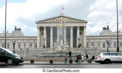 Tourists walk and are photographed in front of Austrian parliament