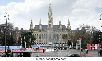 Tourists walk in front of Rathaus near road where go cars and trams