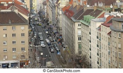 Cars and people go on Favoriten Strasse - pedestrian zone with set of restaurants, shops, caf