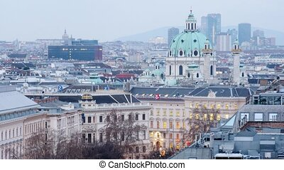 Domes of Karlskirche Church extend upward above city...