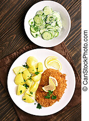 Viennese schnitzel with boiled potato and cucumber salad on...