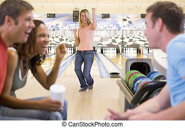 vier, jonge volwassenen, juichen, in, een, bowling steeg